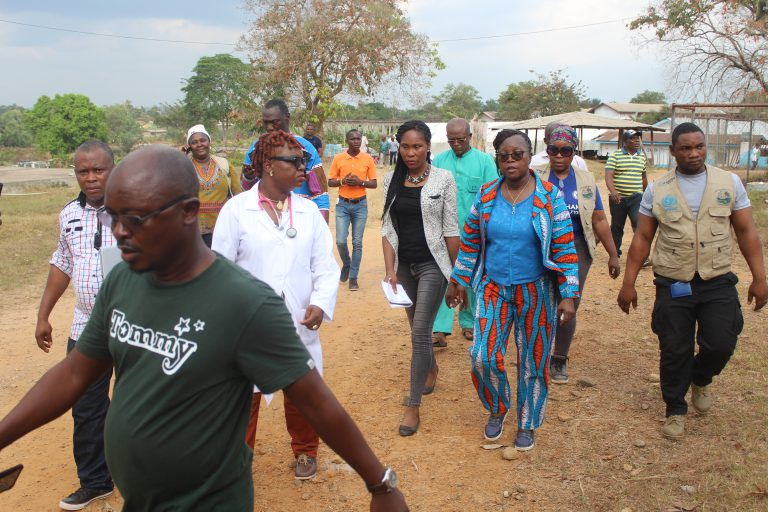 Health Minister walking to health facility in Bomi.